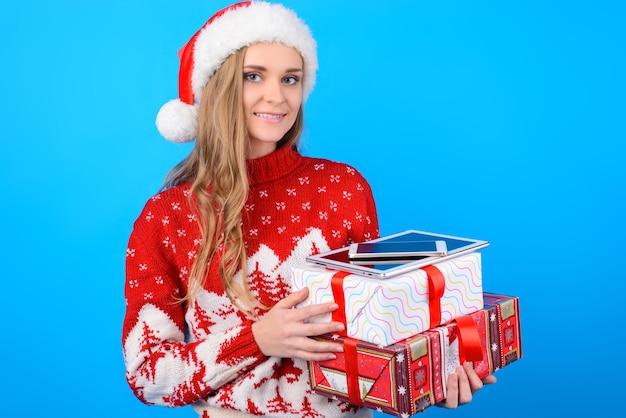 Lachende gelukkig vreugdevolle aantrekkelijke jonge vrouw wacht op kerstmis met grote geschenkdozen, smartphone en digitale tafel in haar handen, geïsoleerd op helder blauwe achtergrond