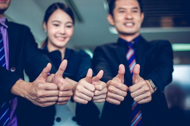 Lachende gelukkig zakenman en ondernemers vieren succes prestatie arm verhoogd en toon duim omhoog concept