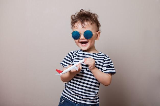 Lachende, gelukkige baby, baby met een klein vliegtuig in zijn handen.