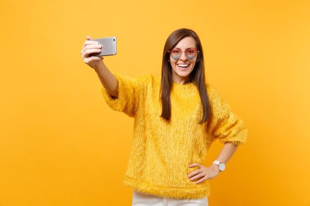 Lachende gelukkige jonge vrouw in bont trui en hart bril doen selfie schot op mobiele telefoon geïsoleerd op heldere gele achtergrond. mensen oprechte emoties, lifestyle concept. reclame gebied.