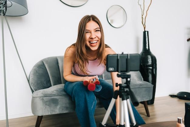 Lachende gelukkige jonge vrouwenvideoblogger die schoonheidsproducten toont via haar blog op sociale media