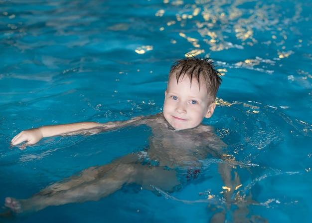 Lachende gelukkige jongen is zwemmen in het zwembad