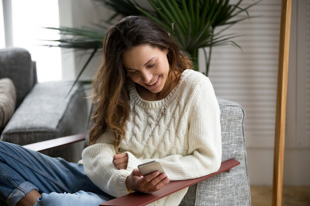 Lachende gelukkige millennial vrouw met smartphone ontspannen op fauteuil