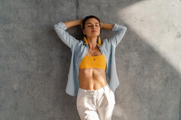 Lachende gelukkige mooie vrouw poseren tegen betonnen muur op zonnige dag met denim shirt, gele top en witte broek