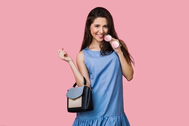 Lachende gelukkige vrouw in blauwe katoenen zomerjurk poseren op roze achtergrond, met tas en zonnebril, vakantiestijl, jong en mooi