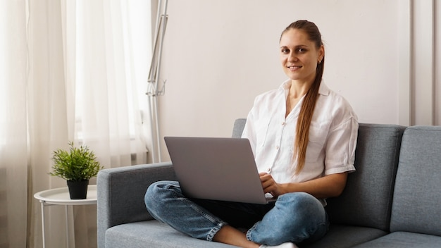 Lachende gelukkige vrouw zittend op de bank en met behulp van laptop. het concept van werken of studeren op afstand tijdens quarantaine.
