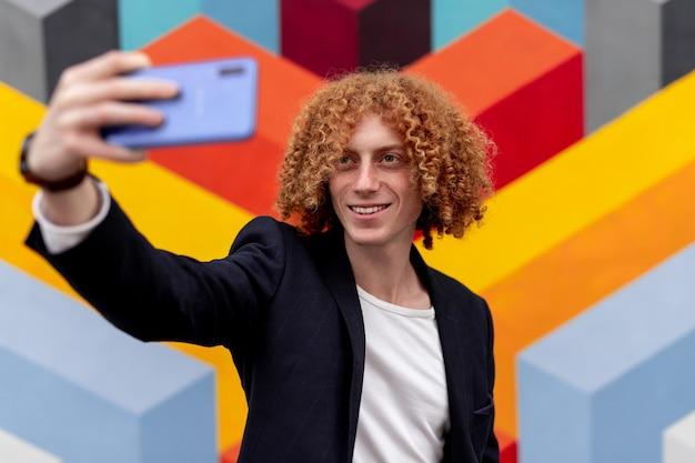 Lachende gember man in trendy outfit selfie te nemen op smartphone