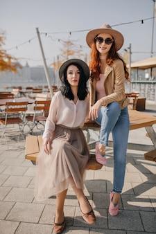 Lachende gember vrouw in spijkerbroek zittend op tafel op terras