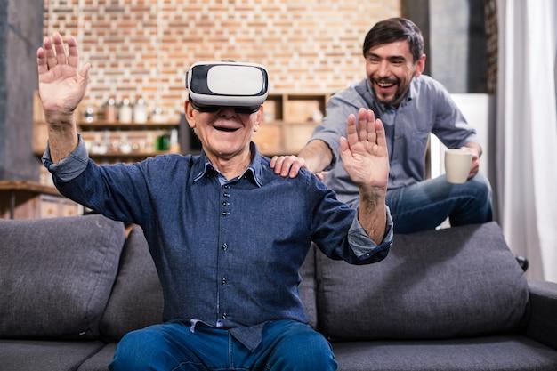 Lachende gepensioneerde man thuis rusten met zijn zoon tijdens het gebruik van vr-bril