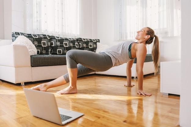 Lachende gespierde fitness instructeur om thuis te zitten op de vloer en rekoefeningen te tonen