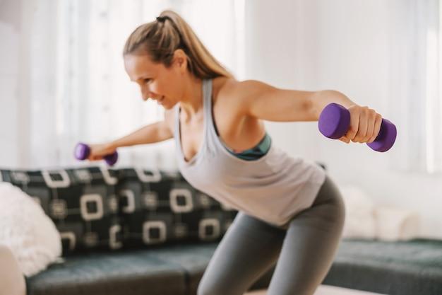 Lachende gespierde sportvrouw halters opheffen en thuis fitness oefeningen doen.