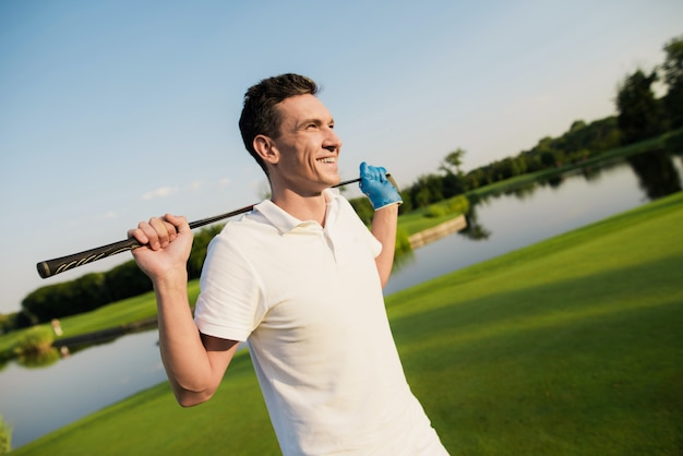 Lachende golfspeler in wit heeft luxueuze sporten.