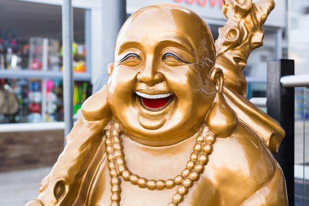 Lachende gouden boeddha buiten. decoratief beeld lachende boeddha of hotei
