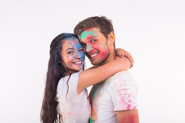Lachende grappige vrouw en man poseren met veelkleurige poeder op hun