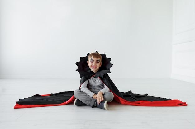 Lachende halloween-jongen met vleermuisachtige kraag voor posters