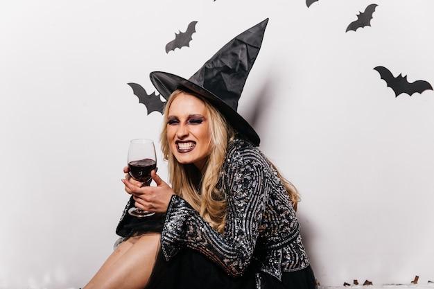 Lachende heks die bloed drinkt. blondemeisje die in tovenaarshoed van wijn genieten bij halloween.