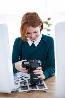 Lachende hipster fotograaf kijken naar foto's op haar camera, zittend aan haar bureau