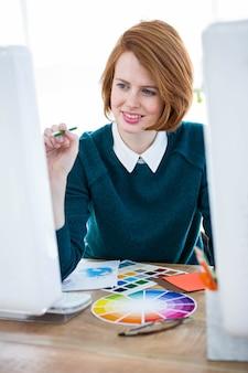 Lachende hipster-fotograaf, zittend aan haar bureau, kijkend naar kleurenwielen
