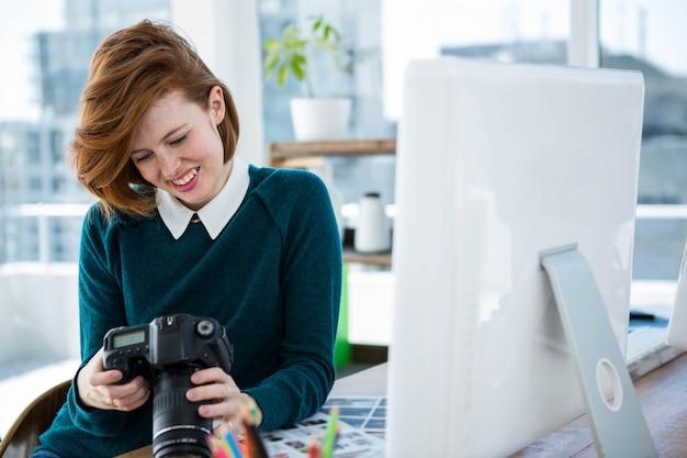 Lachende hipster fotograaf, zittend aan haar bureau, op zoek naar haar camera