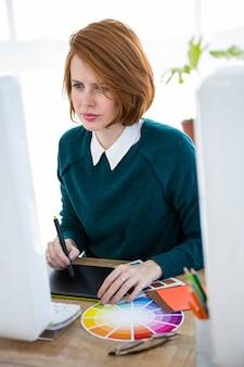 Lachende hipster ontwerper, zittend aan haar bureau, op een digitale tablet