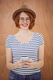 Lachende hipster vrouw met een mobiele telefoon en staande voor een houten