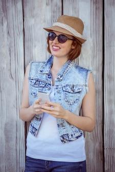 Lachende hipster vrouw op haar smartphone