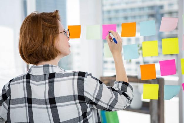 Lachende hipster vrouw plak notities op een prikbord in het kantoor