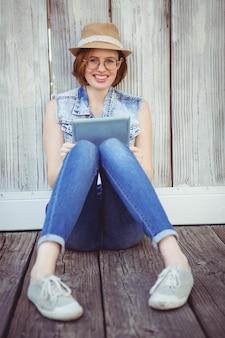 Lachende hipster vrouw, zittend op de grond, met een tablet-computer