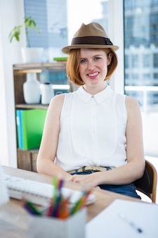 Lachende hipster zakelijke vrouw zit aan haar bureau, het dragen van een trilby