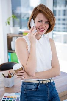 Lachende hipster zakelijke vrouw zit aan haar bureau, met een koffiekopje