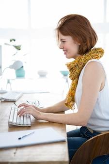 Lachende hipster zakenvrouw typen op haar computer op kantoor