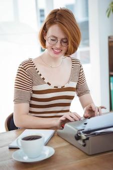 Lachende hipster zit aan een bureau met koffie en een typemachine