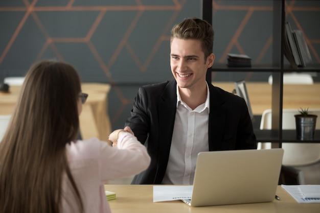 Lachende hr werkgever handshaking succesvolle sollicitant huren of groeten