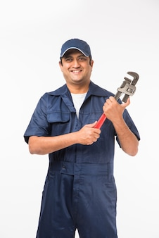Lachende indiase loodgieter met waterpomptang of sanitair spanner, gekleed in een blauw uniform met dop met duimen omhoog. geïsoleerd