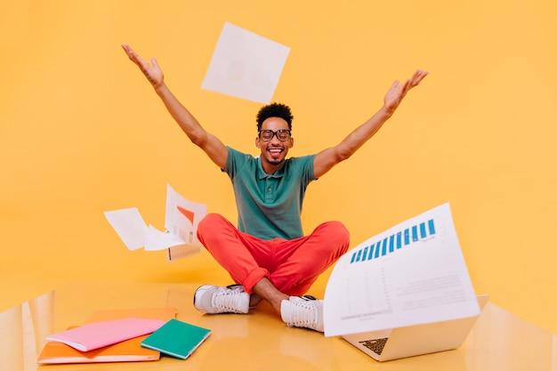 Lachende internationale student die papieren weggooit. indoor foto van afrikaanse mannelijke freelancer zittend op de vloer met laptop.