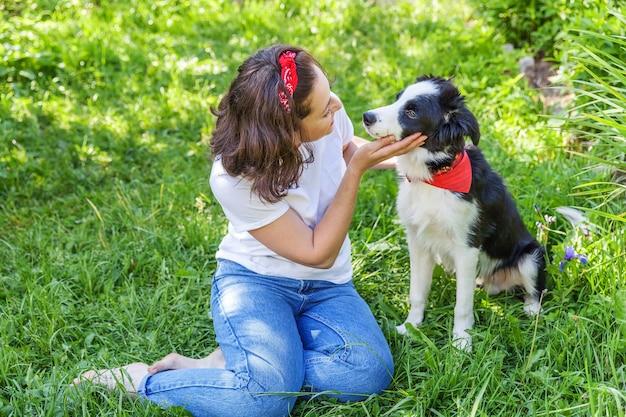 Lachende jonge aantrekkelijke vrouw spelen met schattige puppy hondje bordercollie in zomertuin of stadspark buiten