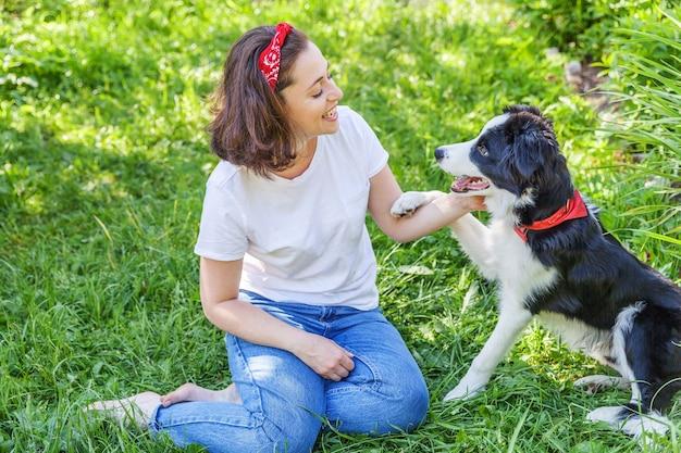 Lachende jonge aantrekkelijke vrouw spelen met schattige puppy hondje bordercollie in zomertuin