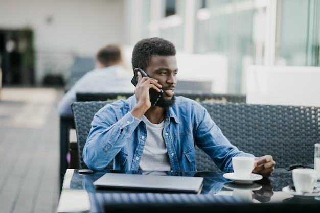 Lachende jonge afrikaanse man koffie drinken en praten op mobiele telefoon zittend in café
