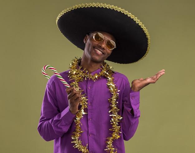 Lachende jonge afro-amerikaanse man met mexicaanse hoed en bril met klatergoud slinger rond de nek met kerst candy cane kijken naar camera met lege hand geïsoleerd op olijfgroene achtergrond