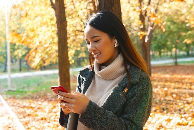 Lachende jonge aziatische vrouw dragen jas buiten wandelen in het park, luisteren naar muziek met koptelefoon, mobiele telefoon te houden