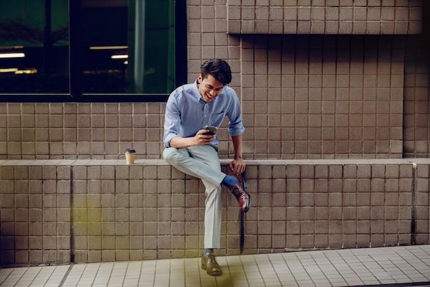 Lachende jonge aziatische zakenman met behulp van mobiele telefoon in de stad