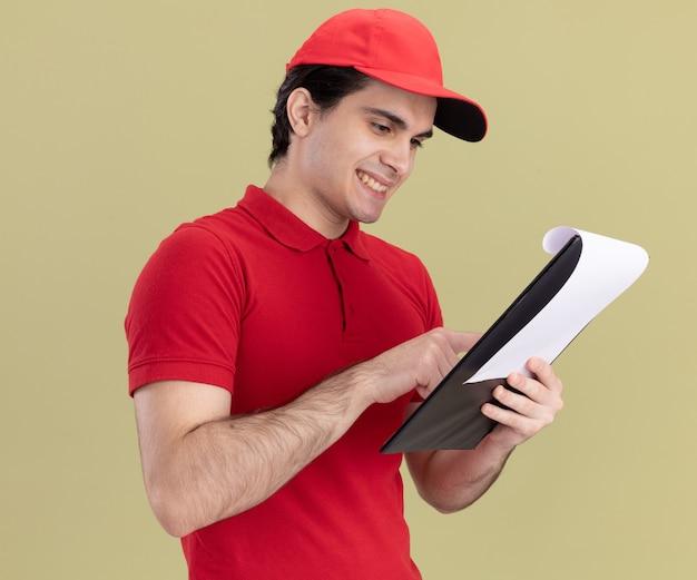 Lachende jonge bezorger in rood uniform en pet staande in profielweergave houden en kijken naar klembord wijzende vinger erop geïsoleerd op olijfgroene muur