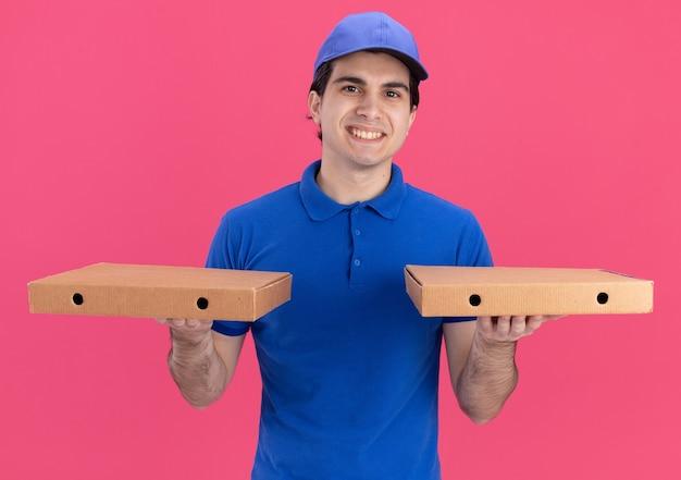 Lachende jonge blanke bezorger in blauw uniform en pet met pizzapakketten geïsoleerd op roze muur