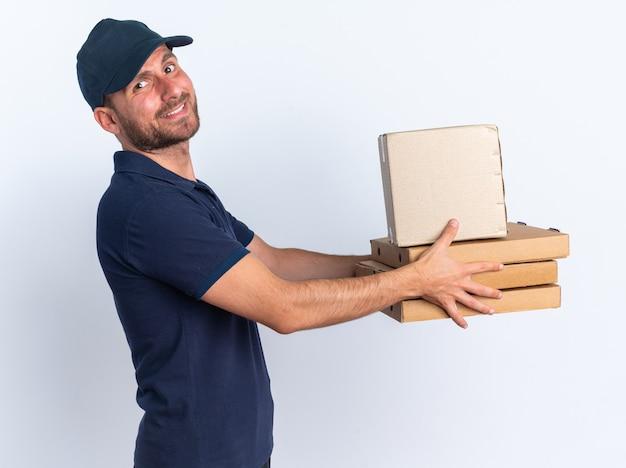 Lachende jonge blanke bezorger in blauw uniform en pet staande in profielweergave pizzapakketten en kartonnen doos uitrekkend kijkend naar camera geïsoleerd op witte muur