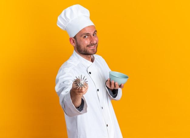 Lachende jonge blanke mannelijke kok in chef-kok uniform en pet staande in profielweergave met kom kijken en wijzend op camera met garde geïsoleerd op oranje muur met kopieerruimte
