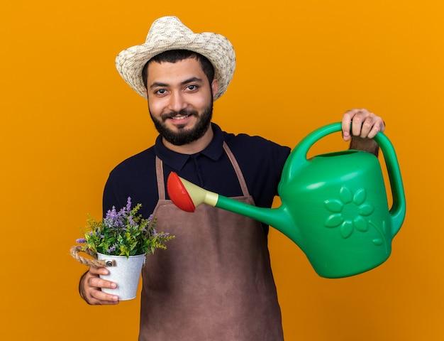 Lachende jonge blanke mannelijke tuinman dragen tuinieren hoed wateren bloemen in bloempot met gieter geïsoleerd op oranje muur met kopie ruimte