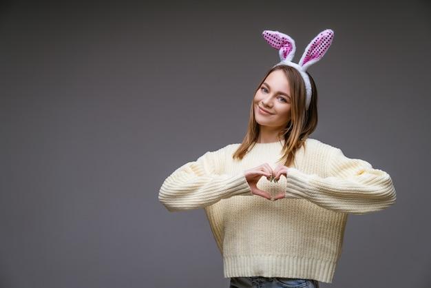Lachende jonge blanke meisje, blond met konijnenoren, toont een hart met twee handen