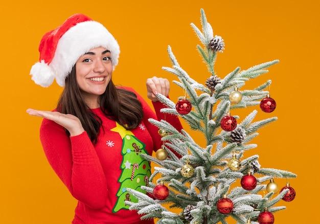 Lachende jonge blanke meisje met kerstmuts houdt hand open staande achter kerstboom geïsoleerd op een oranje achtergrond met kopie ruimte
