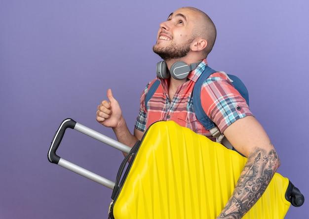 Lachende jonge blanke reiziger man met koptelefoon om zijn nek en met rugzak met koffer en duimen omhoog opzoeken geïsoleerd op paarse achtergrond met kopie ruimte