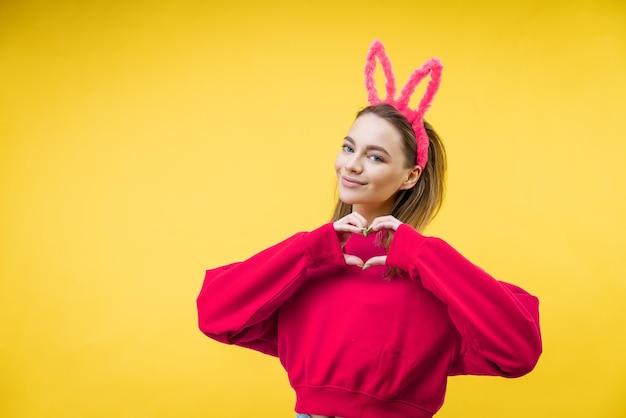 Lachende jonge blanke vrouw, blond met roze konijnenoren, toont een hart met twee handen